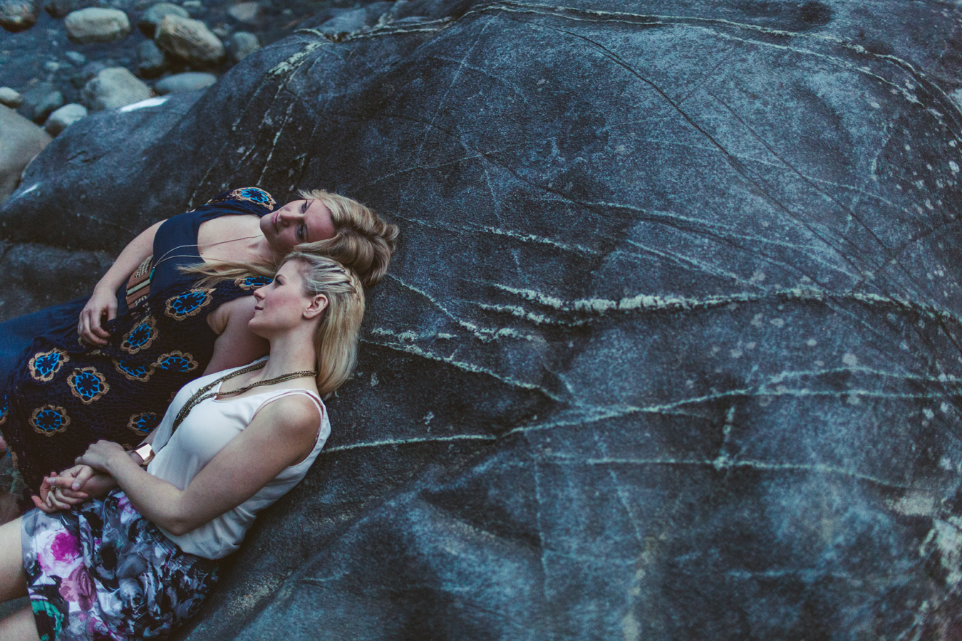 lesbian couple cuddles on a rock