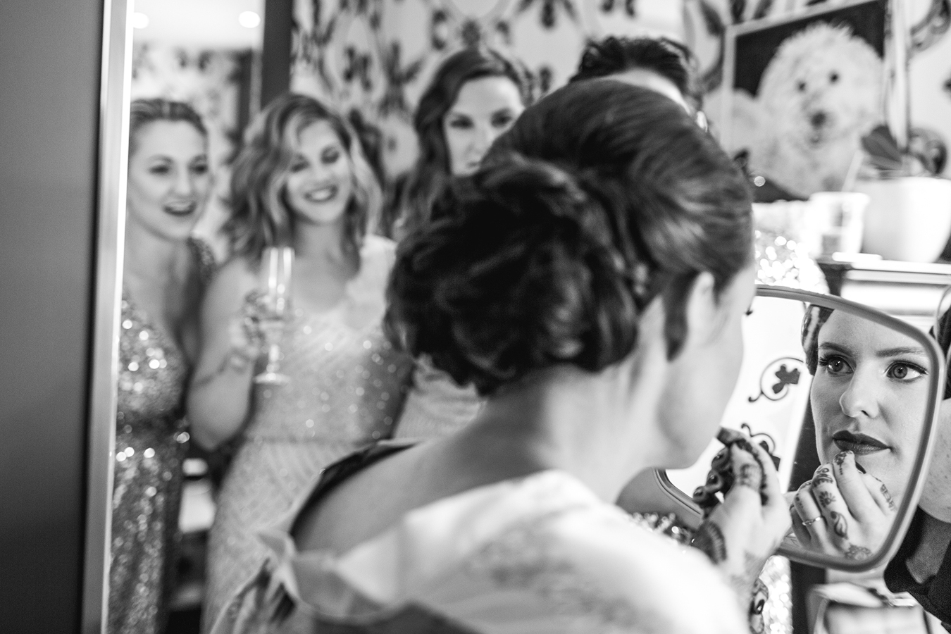bridesmaids watch the bride putting her lipstick on