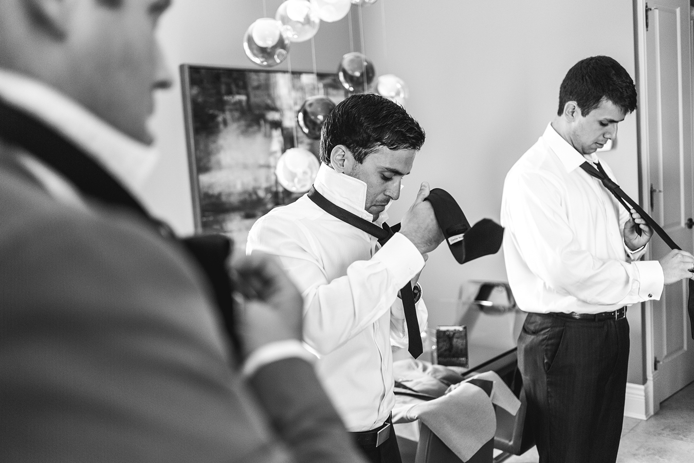 groomsmen tie their ties while getting ready for a Vancouver wedding