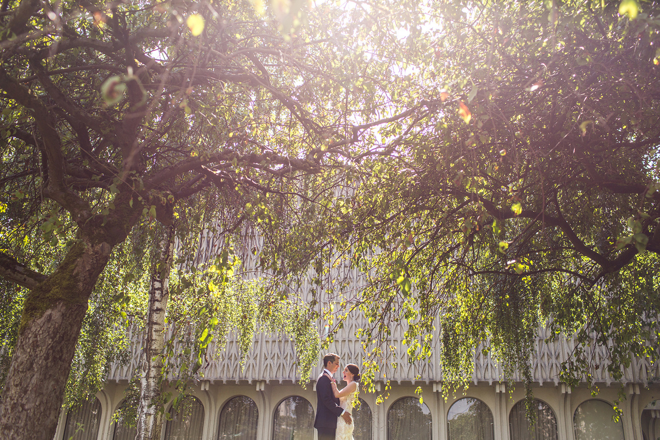 newlyweds share a moment of joy underneath willow trees at Vanier Park in Vancouver BC