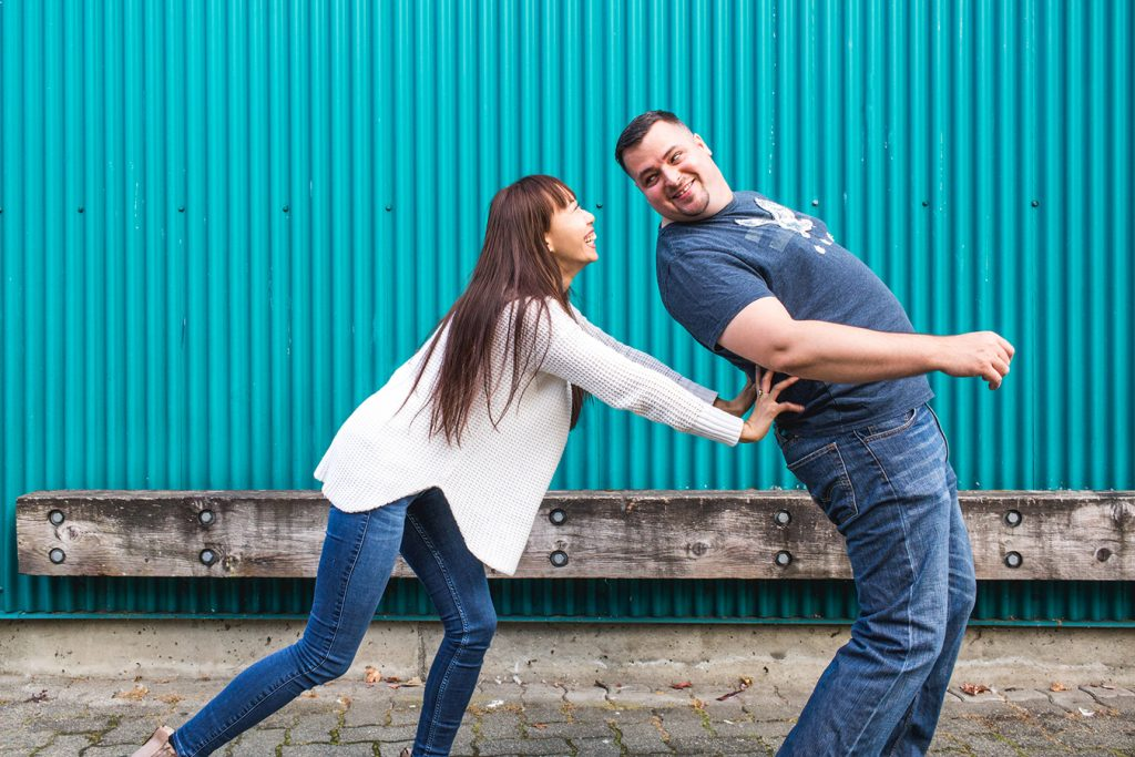 A woman playfully pushes her fiance at Granville Island