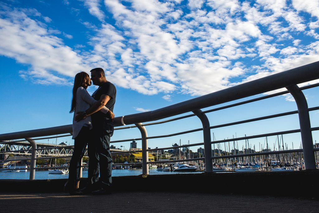 The silhouette of a couple with Granville Island in the background