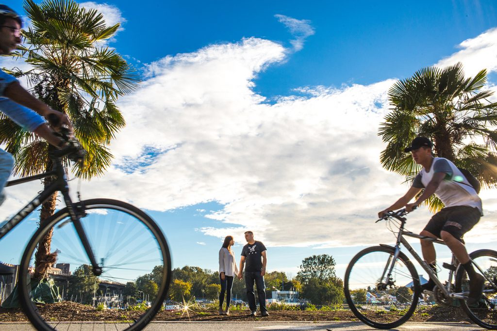 bicycles rush past a couple during their engagement session in Vancouver bc
