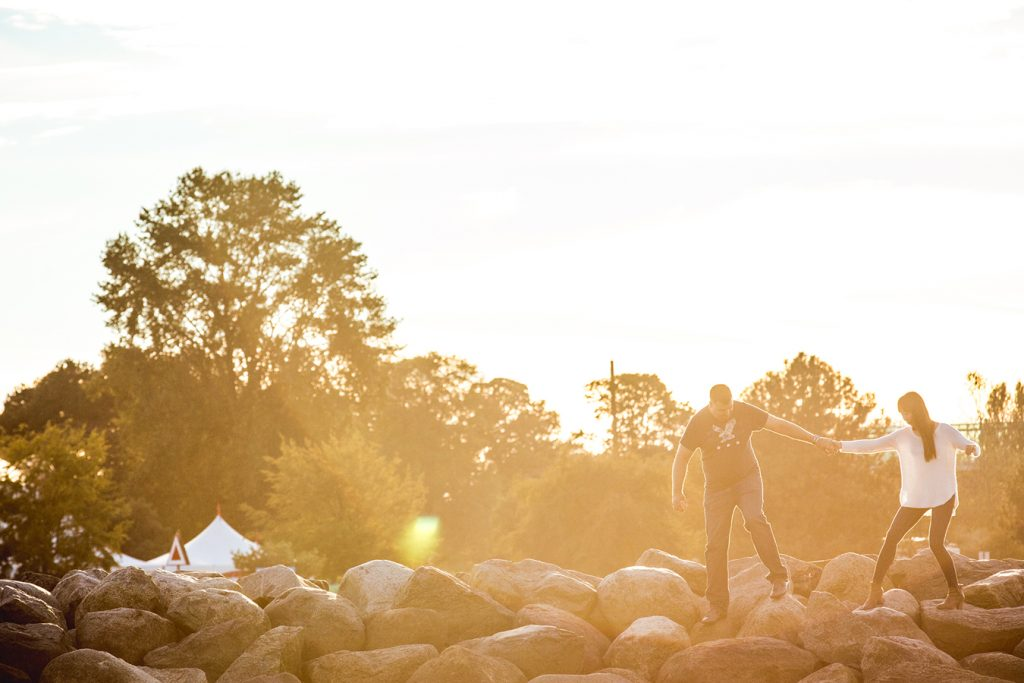 A couple holds hands as they walk across the rocks at sunset