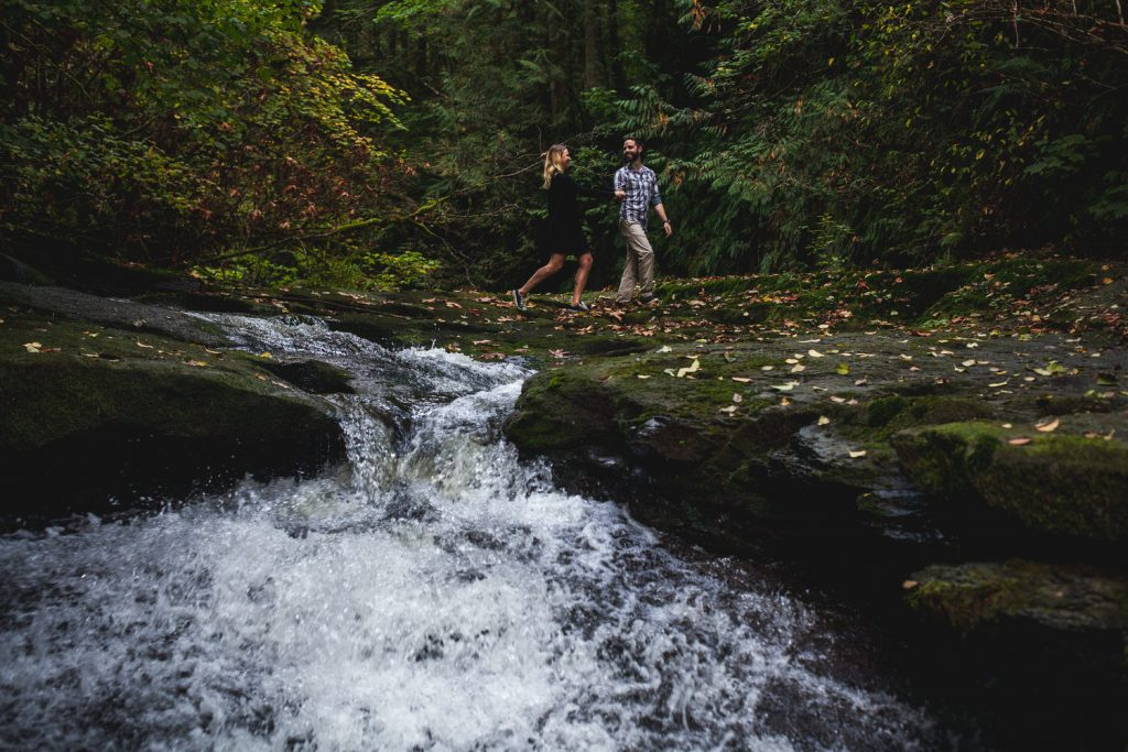 a couple holds hands and walks along the edge of kanaka falls in maple ridge