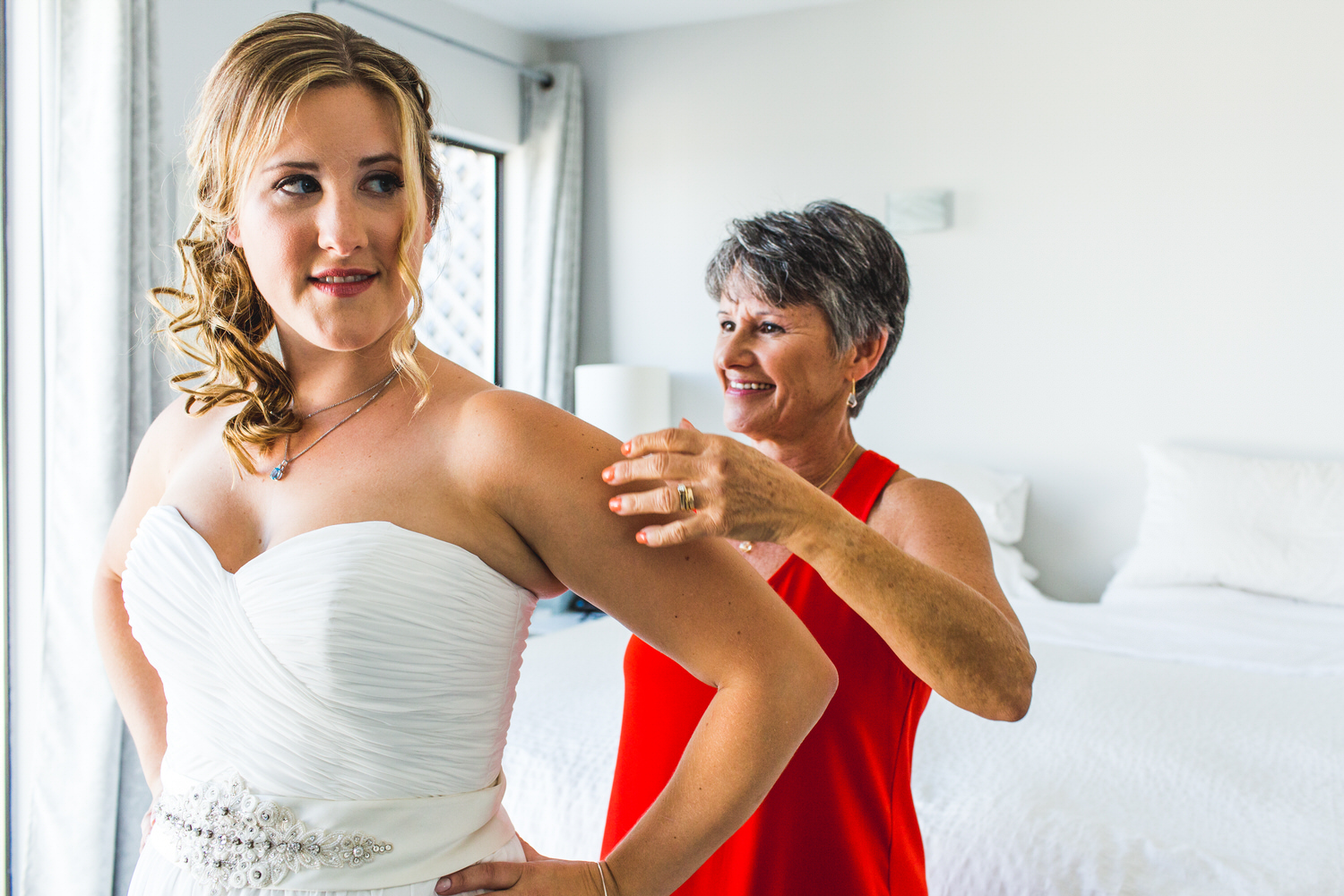 mother helps bride get ready for beach wedding in ladner bc