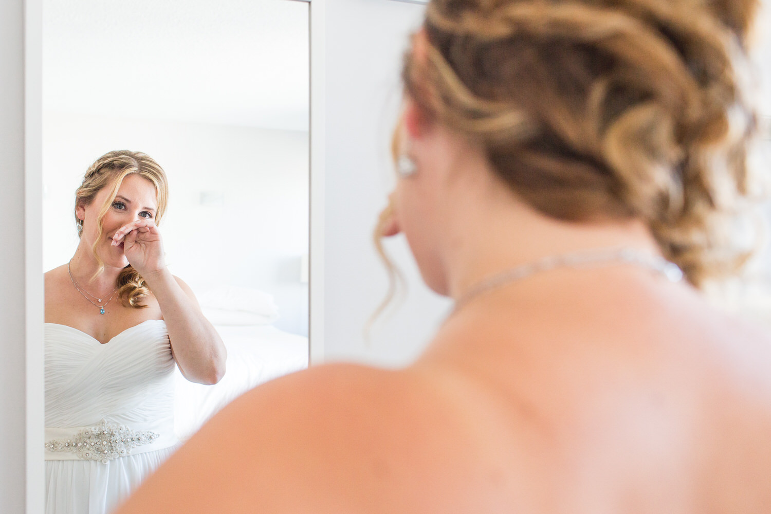bride cries as she sees herself in the mirror