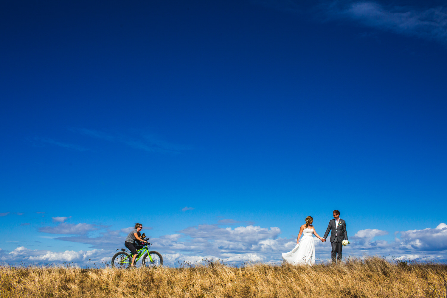 cyclists passes by bride and groom at beach