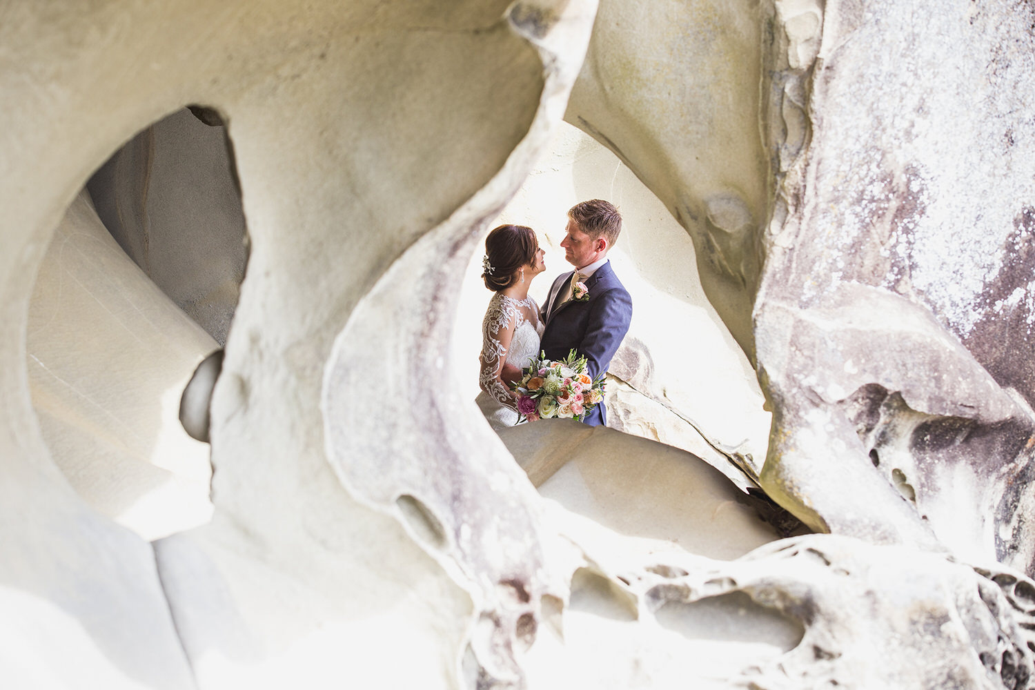 A bride and groom embrace at Retreat Cove on Galiano Island