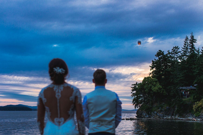 A bride and groom light a lantern near the sea at their Bodega Ridge Wedding