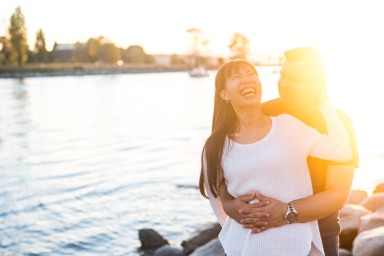 A couple laughs together as the sun sets over the city of Vancouver, during their engagement portraits