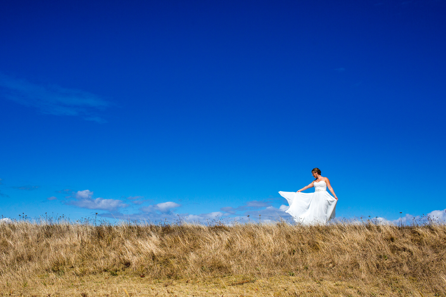 portrait of a bride's wedding dress blowing in the in wind at the beach