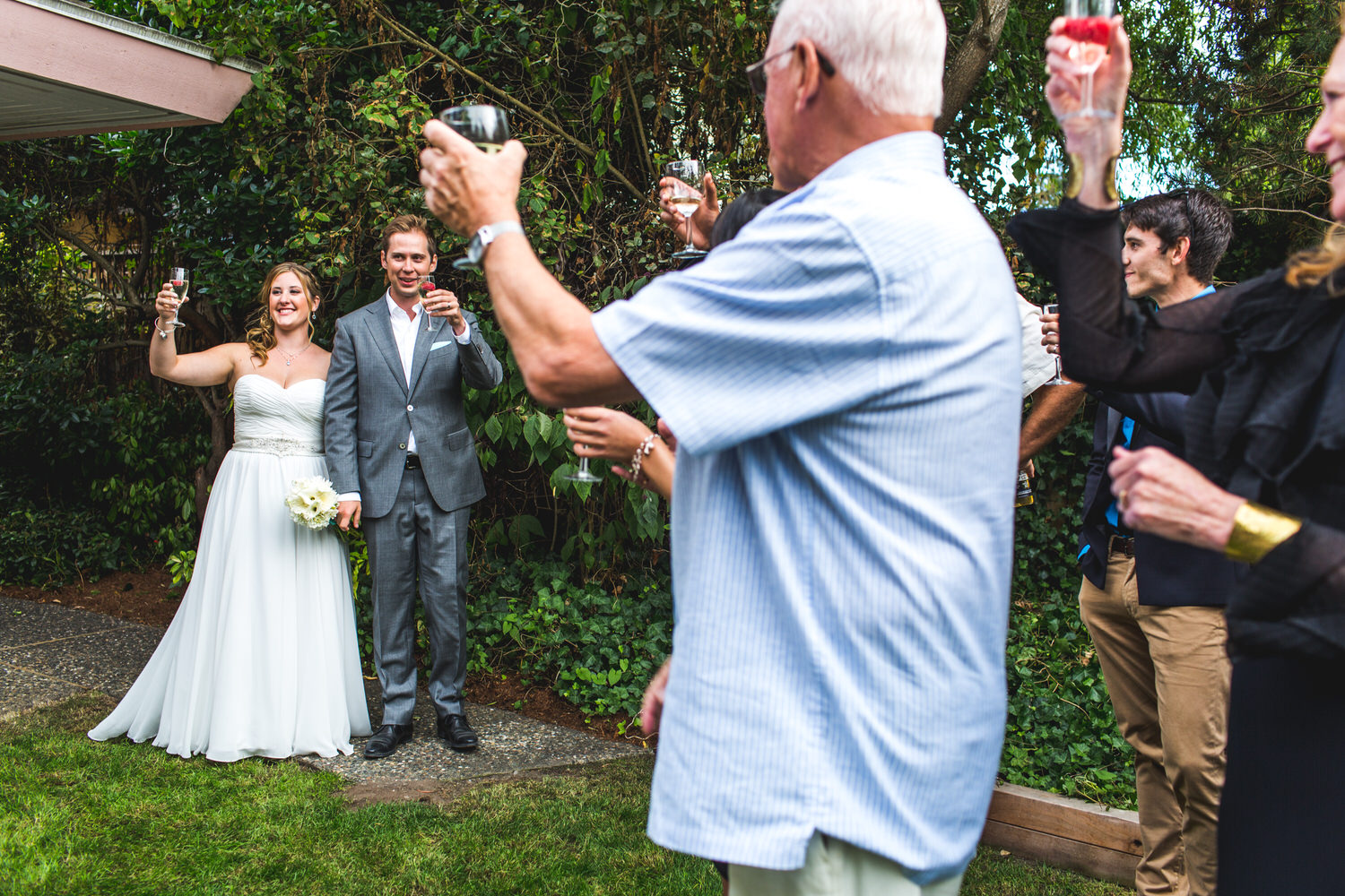 guests toast bride and groom at an intimate backyard wedding